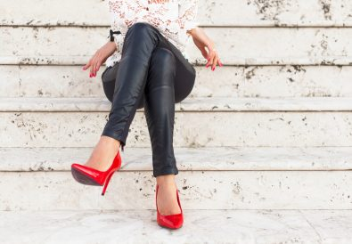 Lady with red high heel shoes sitting on stairs