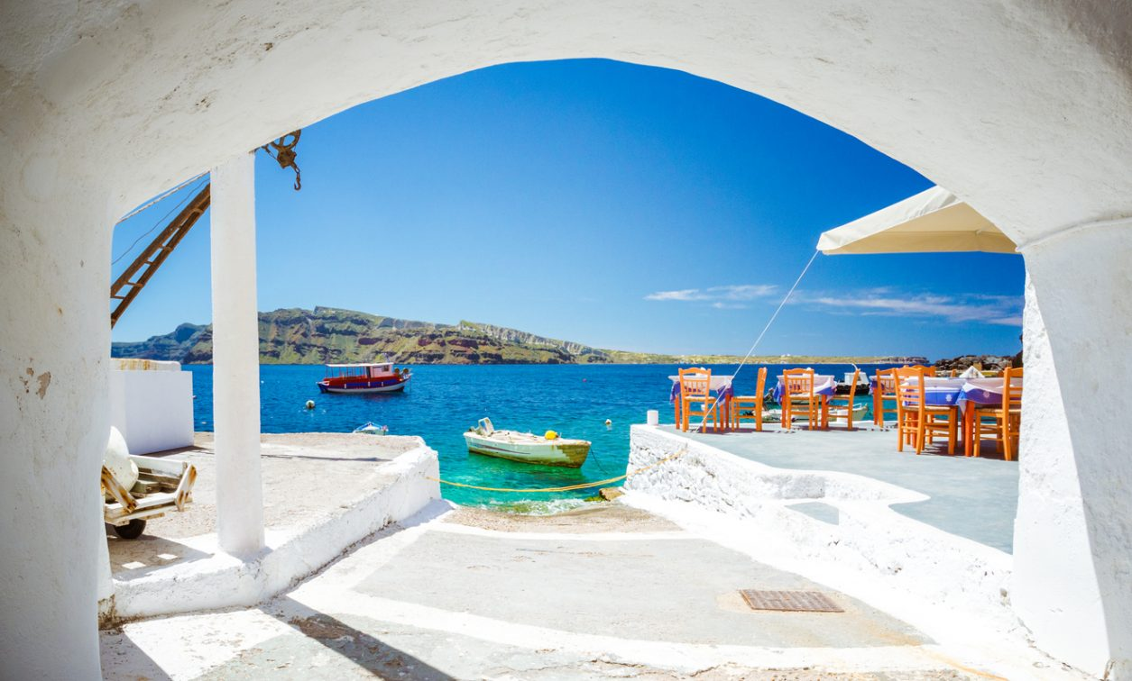 The old harbor of Ammoudi under the famous village of Oia at Santorini, Greece through a frame of an old arched building.