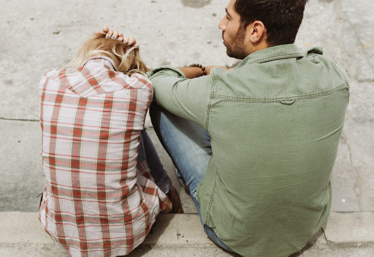 man-and-woman-sitting-on-sidewalk-226166