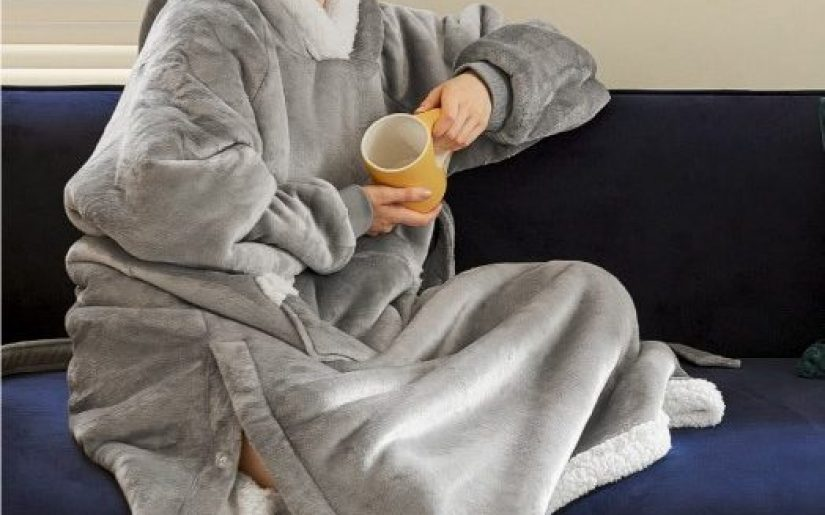 Model-wearing-gray-full-length-Wearable-Blanket-sitting-on-coach-cropped_Bedsure-Amazon-photo_09.2021-524x485